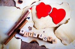 Folha de papel do vintage velha, dois corações vermelhos, lápis de madeira e palavras com amor em cubos na serapilheira, fundo do Fotografia de Stock Royalty Free