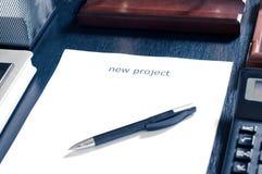 Folha de papel em uma tabela com o projeto novo da palavra Introduza seu texto Imagens de Stock
