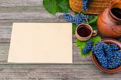 A folha de papel horizontal coloca ao lado da cesta, da bacia com uvas, do frasco e do copo com vinho na madeira rústica Fundo da imagens de stock