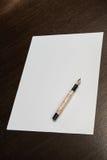Folha de papel na tabela e em uma pena de fonte Imagem de Stock Royalty Free