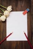 Folha de papel vazia, lápis, e flores na mesa de madeira escura Foto de Stock