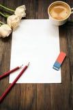 Folha de papel vazia, lápis, eliminador, flores e xícara de café na mesa de madeira escura Foto de Stock