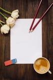 Folha de papel vazia, lápis, flores e xícara de café na mesa de madeira escura Fotografia de Stock