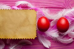 Folha de papel vazia, ovos da páscoa coloridos e penas fotos de stock