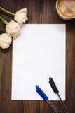 Folha de papel vazia, penas, flores e xícara de café na mesa de madeira escura Imagens de Stock Royalty Free