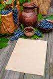 A folha de papel vertical coloca ao lado da cesta, da bacia com uvas, do frasco e do copo com vinho na madeira rústica Fatura de  foto de stock