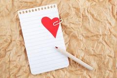 Folha do caderno com um coração e do lápis no papel amarrotado. Imagens de Stock