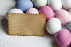 Folha do papel vazio e ovos coloridos na tabela de madeira Fotos de Stock Royalty Free