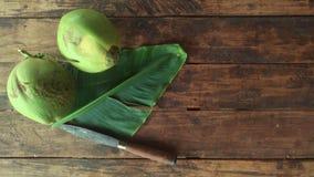 A folha e a faca frescas da banana do coco no assoalho de madeira na casa imagens de stock royalty free