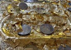 Folha e moedas de ouro na pegada da Buda Foto de Stock Royalty Free