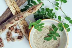 A folha e a semente de Moringa grinded no fundo branco Imagem de Stock
