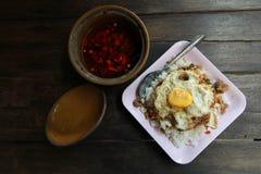 Folha fritada da manjericão com galinha e ovos fritos no arroz em b de madeira Imagem de Stock