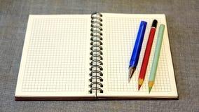 Folha limpa do papel do caderno e de um lápis com uma pena Fotos de Stock Royalty Free