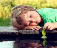 Folha-navio verde na mão das crianças na água, menino no jogo do parque com o barco no rio imagem de stock