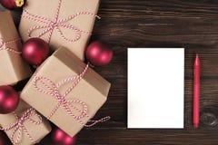 Folha vazia branca com presentes de Natal na opinião superior do fundo de madeira, configuração lisa Lista de presentes do Natal, Imagens de Stock Royalty Free
