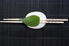 Folha verde em chopsticks   Imagem de Stock Royalty Free