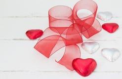 A folha vermelha e de prata cobriu chocolates do Valentim do coração no branco Imagem de Stock Royalty Free
