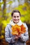 Folhas bonitos da terra arrendada da mulher nova na floresta Imagens de Stock