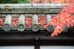 Folhas de bordo vermelhas no telhado japonês Foto de Stock Royalty Free