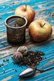 Folhas de chá e maçã vermelha no fundo de madeira Fotografia de Stock Royalty Free