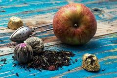 Folhas de chá e maçã vermelha no fundo de madeira Foto de Stock