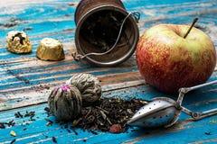 Folhas de chá e maçã vermelha no fundo de madeira Imagens de Stock Royalty Free
