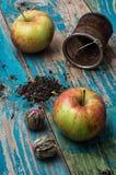 Folhas de chá e maçã vermelha no fundo de madeira Imagem de Stock Royalty Free