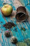 Folhas de chá e maçã vermelha no fundo de madeira Fotos de Stock