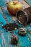 Folhas de chá e maçã vermelha no fundo de madeira Fotografia de Stock