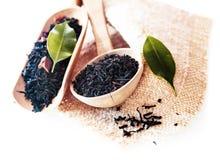 Folhas de chá orgânicas frescas em colheres de madeira fotografia de stock
