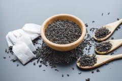 Folhas de chá pretas em uma bacia de madeira imagens de stock