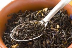 Folhas de chá verde em uma bacia com colher Fotografia de Stock Royalty Free