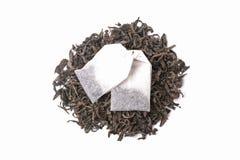 Folhas de chá verdes e saquinhos de chá isolados no fundo branco Imagens de Stock Royalty Free