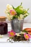 Folhas de chá verdes secas do jasmim com flores do jasmim, com as flores de rosas e do doce de framboesa selvagens Fotografia de Stock Royalty Free