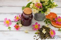 Folhas de chá verdes secas do jasmim com flores do jasmim, com as flores de rosas e do doce de framboesa selvagens Imagem de Stock