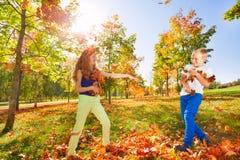 Folhas de jogo do jogo da menina e do menino na floresta foto de stock royalty free