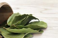 Folhas de louro aromáticas secadas em uma bacia de madeira na tabela rústica de madeira branca Foto da colheita da baía do louro  Fotografia de Stock Royalty Free