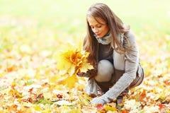 Folhas de outono da picareta da mulher Fotografia de Stock
