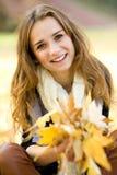 Folhas de outono da terra arrendada da mulher Fotos de Stock Royalty Free