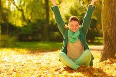 Folhas de outono de jogo da mulher feliz no parque Imagens de Stock Royalty Free