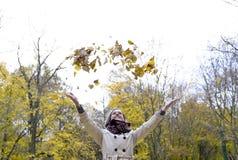Folhas de outono de jogo da mulher nova Foto de Stock Royalty Free