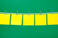 Folhas de papel amarelas vazias na corda Imagens de Stock