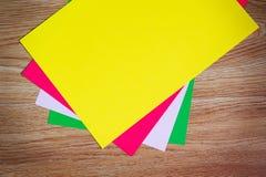 Folhas de papel coloridas empilhadas em um assoalho de madeira Fotografia de Stock