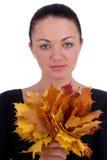 Folhas de plátano da laranja do outono da terra arrendada da menina foto de stock