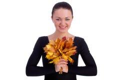Folhas de plátano da laranja do outono da terra arrendada da menina fotografia de stock