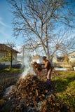 Folhas de queimadura dos mortos do fazendeiro idoso Imagens de Stock Royalty Free