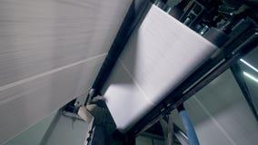 Folhas de rolamento do jornal em um transporte especial, vista inferior