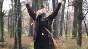 Folhas de sorriso e de jogo da jovem mulher feliz no ar vídeos de arquivo