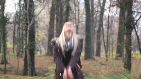 Folhas de sorriso e de jogo da jovem mulher feliz no ar filme