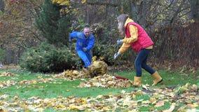 Folhas do ancinho da mulher O homem faz a confusão na jarda do jardim Pares brincalhão 4K filme